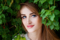 Happy smiling beautiful young woman surrounded by green leaves Royalty Free Stock Photos