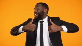 Happy smiling black guy in suit making thumbs-up, salesman promoting goods stock video footage