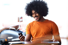 Happy smiling black man looking at mobile phone Stock Images