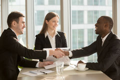 Happy smiling black and white businessmen handshaking after sign. Ing contract at multi-ethnic meeting with businesswoman, multiracial partners shaking hands Royalty Free Stock Photos