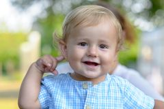 Happy smiling blond baby boy outdoors stock photography
