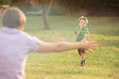 Happy smiling blond caucasian kid outdoor at park running and play with his mum Royalty Free Stock Photo