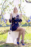 Happy Smiling Blond Female Relaxing In Spring Forest on Swing. W Stock Image