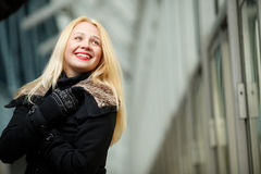 Happy smiling blond woman in black down jacket and mittens royalty free stock photo
