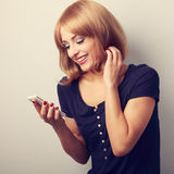Happy smiling blond woman reading sms in mobile phone. Toned clo Royalty Free Stock Images