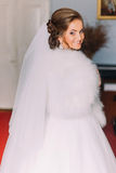 Happy smiling blonde bride from back in white dress, veil and fur boa indoors.  Royalty Free Stock Photography