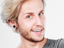 Happy smiling blonde man close up. Fashion, happiness, joy concept. Happy smiling blonde man wearing grey t shirt, studio shot close up grey background Royalty Free Stock Photos