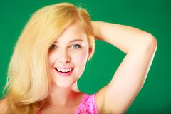 Happy smiling blonde woman in pink top. Dyeing, hairstyling, feminity, female beauty concept. Happy blonde woman in pink top holding hand behind head. Studio royalty free stock images