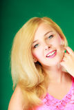Happy smiling blonde woman in pink top. Dyeing, hairstyling, feminity, female beauty concept. Happy blonde woman in pink top. Studio shot on green background royalty free stock photography
