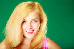 Happy smiling blonde woman in pink top. Dyeing, hairstyling, feminity, female beauty concept. Happy blonde woman in pink top. Studio shot on green background stock photography