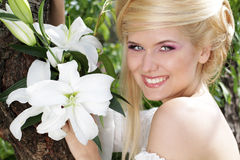 Happy Smiling blonde young woman with lily. Happy Smiling blonde young woman with white lily, nature Royalty Free Stock Photography