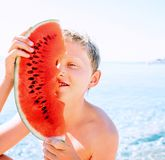 Happy smiling boy with big watermelon segment sits near the sea royalty free stock photo