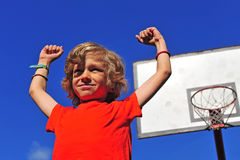 Happy smiling boy celebrating victory with hands in the air. And basketball hoop on background Stock Photo