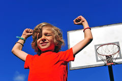 Happy smiling boy celebrating victory with his hands up. With basketball hoop on background Stock Photography