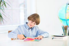 Happy smiling boy cutting colorful paper with scissors Stock Image