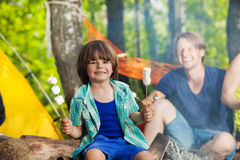 Happy smiling boy eating marshmallows at campsite royalty free stock images