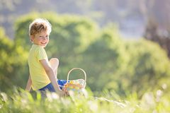 Kid at easter. Happy smiling boy excited after easter egg hunt in the park with basket full of eggs, spring concept Stock Photo