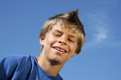 Happy smiling boy with fashionable hairstyle. A happy smiling 10-years old boy with a fashionable hairstyle photographed in the summer sun with blue sky and tiny royalty free stock photos
