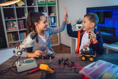 Happy smiling boy and girl constructs technical toy and make robot. Technical toy on table full of details stock photo