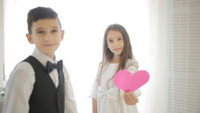 Happy smiling boy and girl holding hands and heart of the show. Valentine`s Day stock video