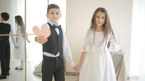 Happy smiling boy and girl holding hands and heart of the show. Valentine`s Day stock footage