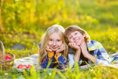 Happy smiling boy and girl lying together on rug Stock Image