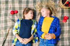 Happy smiling boy and girl lying together on rug Stock Photos