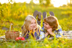 Happy smiling boy and girl lying together on rug Stock Images
