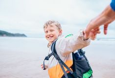 Happy smiling boy holds his father on hand and runs to the surf. Ocean line Royalty Free Stock Photo