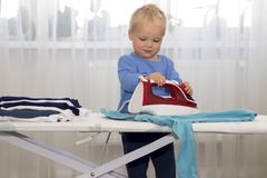 Happy smiling boy ironing clothes. Kid helping with housework. Encouraging Autonomy in children.  Stock Photos
