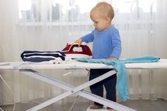 Happy smiling boy ironing clothes. Kid helping with housework. Encouraging Autonomy in children.  Stock Photo