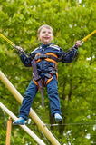 Happy smiling boy is jumping on trampoline. On green background stock image