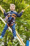 Happy smiling boy is jumping on trampoline. On green background royalty free stock image