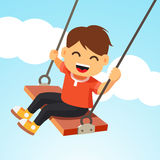 Happy smiling boy kid swinging on a swing Stock Photography