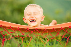 Happy smiling boy lying in hammock Stock Photos