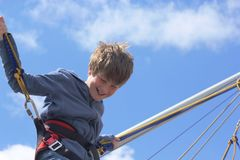 Boy bungee jumping on a trampoline. A happy smiling boy mini bungee jumping on a trampoline Royalty Free Stock Image