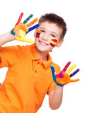 Happy smiling boy with a painted hands and face. Happy smiling boy with a painted hands and face in orange t-shirt - on a white background stock image