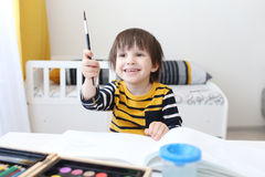 Happy smiling boy paints with brush Royalty Free Stock Images