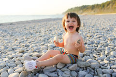 Happy smiling boy on the pebbles beach at sunset Stock Photography
