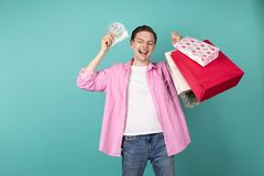 Happy smiling boy in pink shirt with money and shopping backs in hands. Bought a lottery ticket while shopping and won, isolated over blue background stock photo