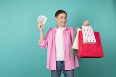 Happy smiling boy in pink shirt with money and shopping backs in hands. Bought a lottery ticket while shopping and won, isolated over blue background royalty free stock photography