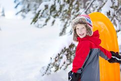 Family winter vacation. Happy smiling boy ready for sledding at winter enjoying cold weather vacation, copy space on left Royalty Free Stock Photography