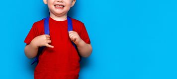 Happy smiling boy in red t-shirt with glasses on his head is going to school for the first time. Child with school bag. Kid on. Blue background background. Back stock photo