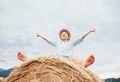 Happy smiling boy sits astride on the haystack Stock Photos