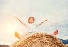 Happy smiling boy sits astride on the haystack Royalty Free Stock Images