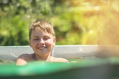 Happy Smiling Boy Splashing In a Swimming Pool on a Hot Sunny Summer Day. Sunbeams, Warm Sun Flare. Blurred Green Background.  royalty free stock photo