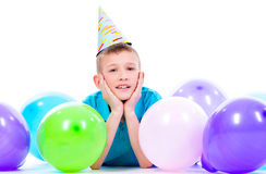 Happy smiling boylying on the floor with colorful balloons. Royalty Free Stock Photography