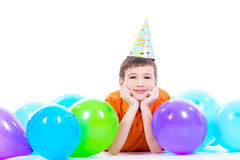 Happy smiling boylying on the floor with colorful balloons. Stock Photo