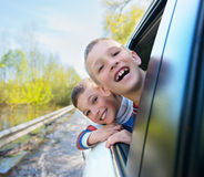Happy smiling boys looks out the car window. Royalty Free Stock Images