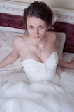 Happy smiling bride dreams in white dress lie in bedroom Royalty Free Stock Photos
